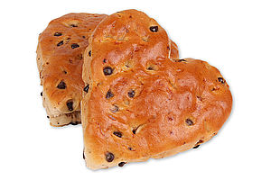 Fully baked milk roll with chocolate chips in a heart shape.