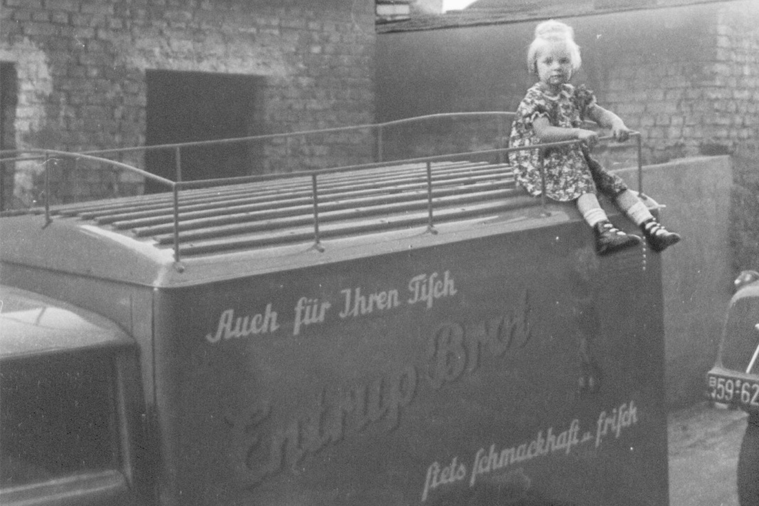 High up even as a child! Doris Entrup on a delivery vehicle of the parental bread factory around 1950.